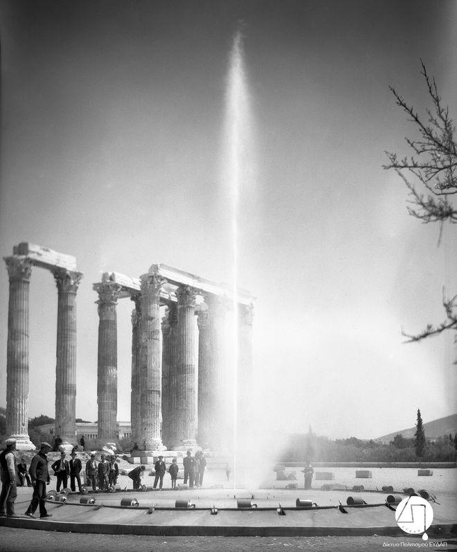 Στιγμιότυπο από την τελετή εγκαινίων του νέου δικτύου ύδρευσης των πόλεων Αθηνών, Πειραιώς και περιχώρων, στους Στύλους του Ολυμπίου Διός, 03 Ιουνίου 1931. Η Ελληνική Εταιρεία Υδάτων διαφημίζεται μέσω της τοποθέτησης πιδάκων νερού στην τελετή των εγκαινίων. ΙΣΤΟΡΙΚΟ ΑΡΧΕΙΟ ΕΥΔΑΠ
