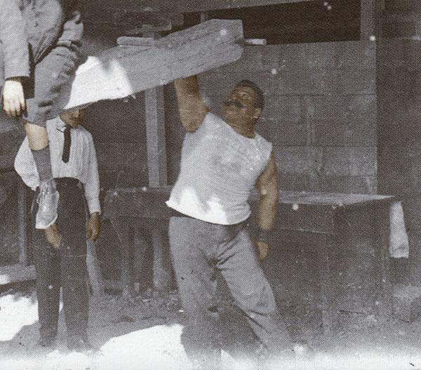 Ο Δημήτρης Τόφαλος σηκώνει με το ένα χέρι ένα ξύλινο δοκάρι που κάθονται πάνω του δύο μικρά παιδιά. (Επιχρωματισμένη λεπτομέρεια από φωτογραφία πριν από το 1906)